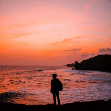 person standing by ocean at sunset